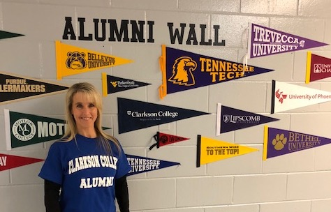 Alumna Joyce Crites ('96) stands near the Clarkson College banner at Westwood Middle School