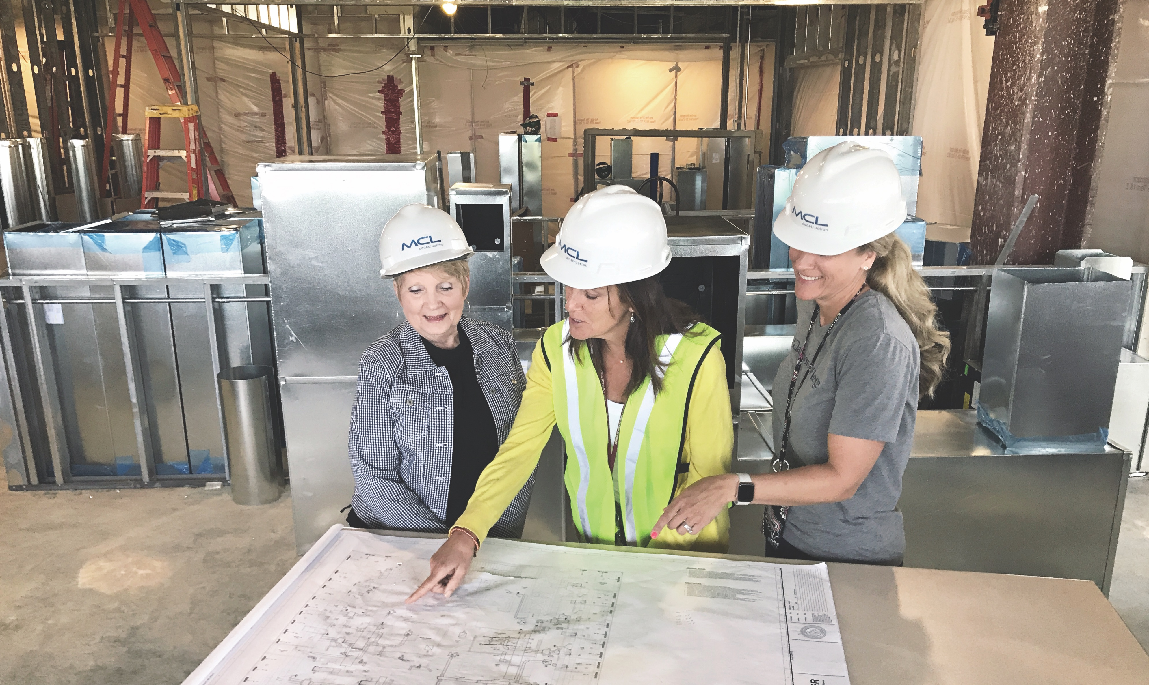 Marsha Cravens, Julie Lawlor and Jennifer Renken discuss the Lab's blueprints.